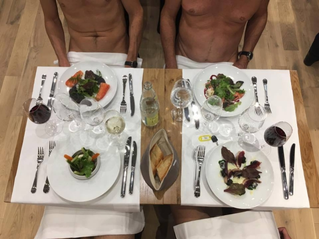 Naked men sitting at restaurant table