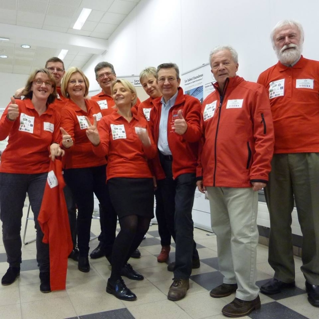 Group of people in red tops smiling to camera