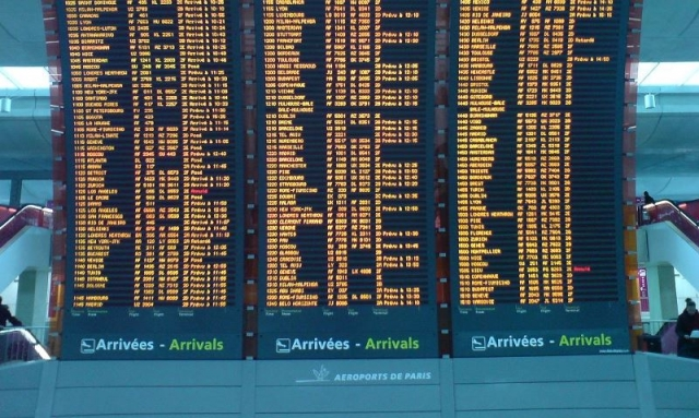 Arrivals board at Paris Charles-de-Gaulle airport with lists of flights in yellow