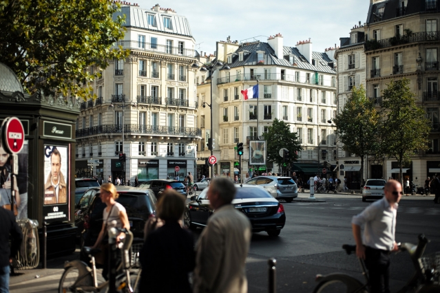 Street scene in Paris in 7th arrondissement with people milling about, a presse kiosk and a French flag