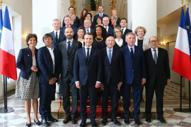 Group of men and women with President Macron and two French flags