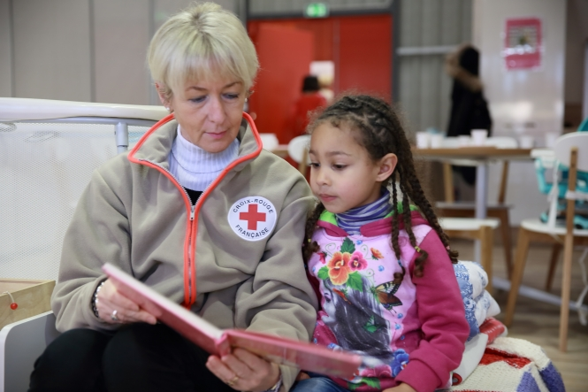 A croix-rouge volunteer reading a book with a young child