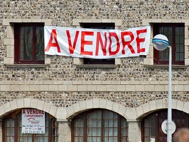 Large French for sale sign - a vendre - on stone-built property with arched windows and lamp standard in front