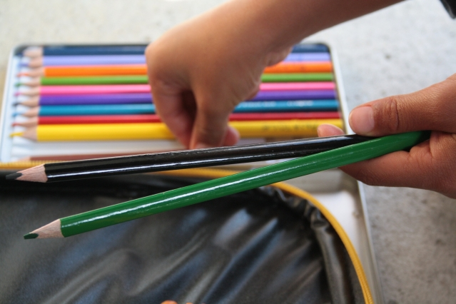 Child puts coloured pencils back in a case