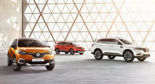 Three cars, orange, red and white in large space with window behind