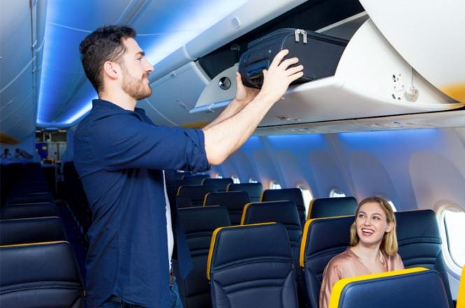 Man puts bag into overhead luggage locker on plane