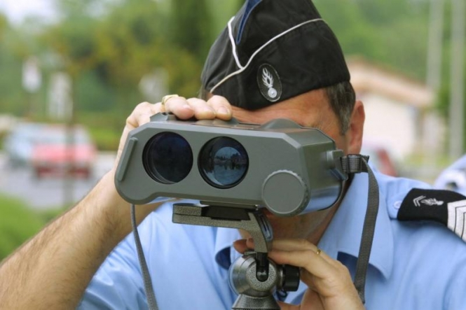 Gendarme with binocular speed camera