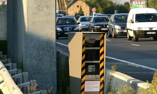 Grey speed camera in France beside busy road with traffic passing - shows that camera only flashes from rear