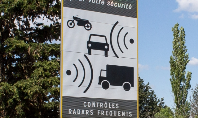 Speed camera warning sign France blue sky