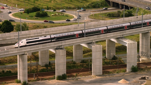 TGV high-speed train on viaduct with road roundabout in background