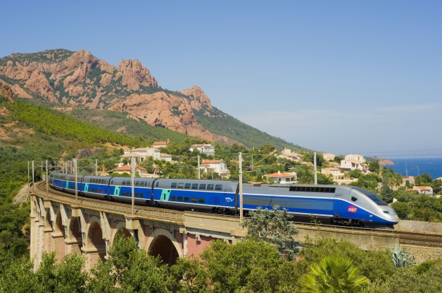 TGV train at speed in front of red rocks