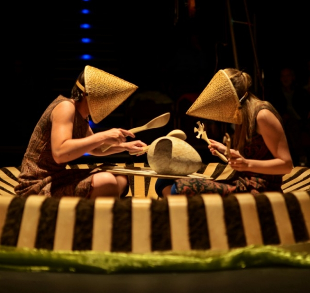 two people on rug with beak-shaped hats over their faces