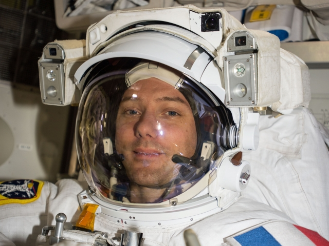 Astronaut in helmet with French flag on shoulder