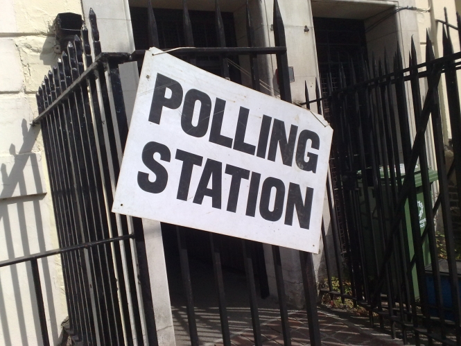 Black and white polling station sign on railing