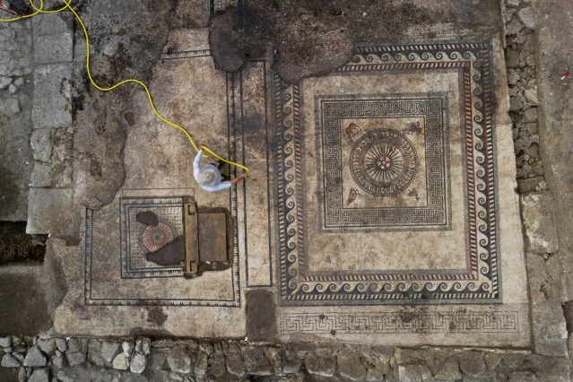 Giant mosaic floor with square design and circle in middle - man hosing down the work