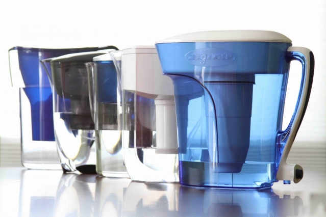 A line-up of clear and blue-tinted water jugs with filters and lids