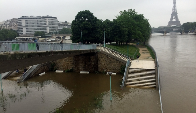 flood waters breaching the banks of the River Seine in Paris, with the Eiffel Tower in the distance