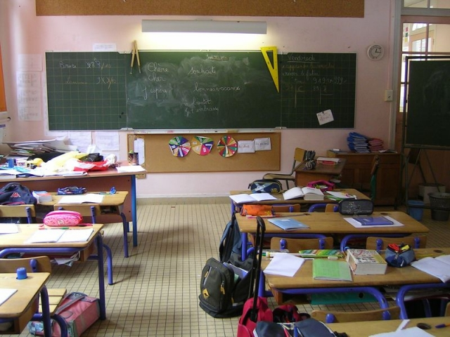 a school classroom with desks covered with books and bags