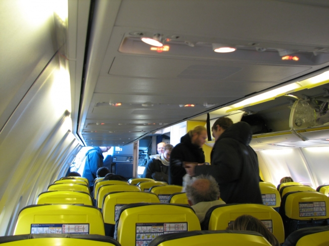 Aircraft passengers loading bags into overhead storage lockers before take-off