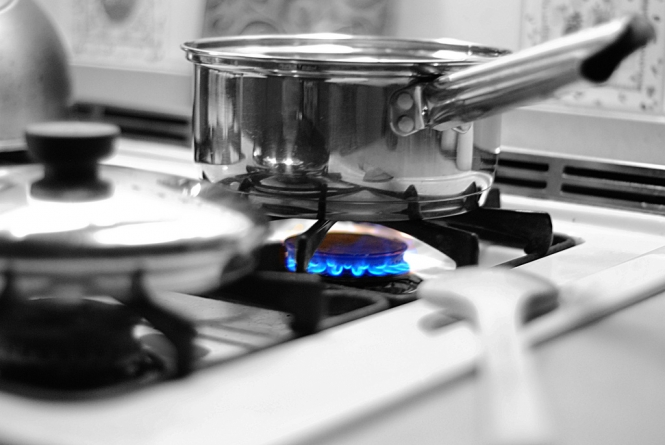 A pan on a gas stove with the burner lit