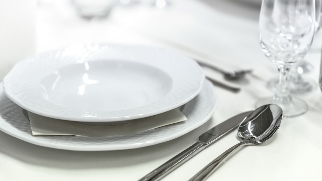 a place setting for dinner with a white bowl and plate