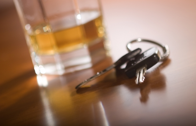 A glass filled with an alcoholic drink pictured next to a set of car keys