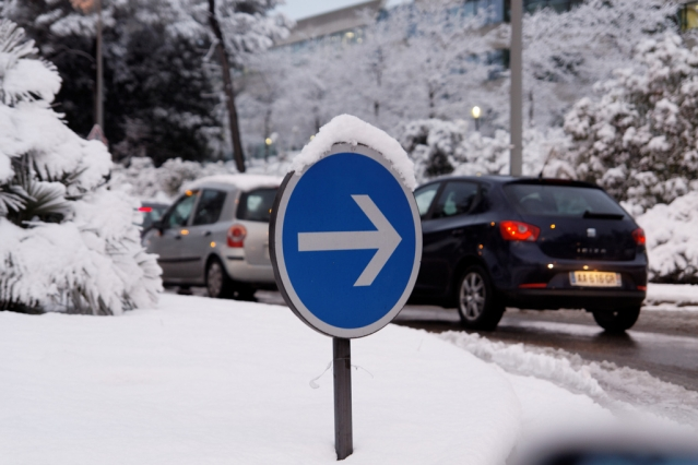 Cars carefully navigate the slippery road at a snow-covered roundabout