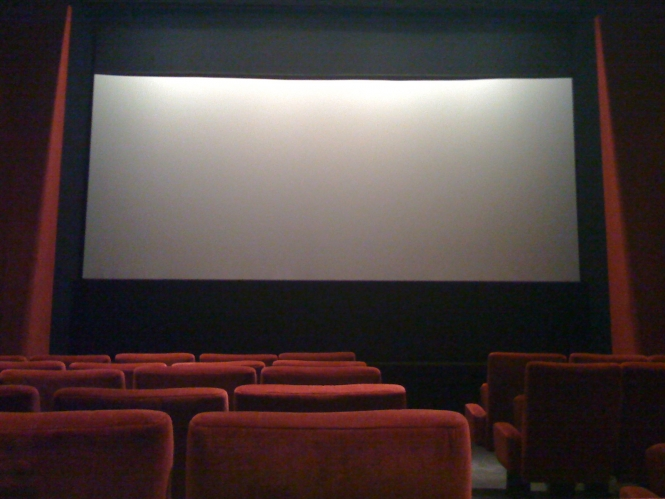 empty cinema seats in front of a blank cinema screen