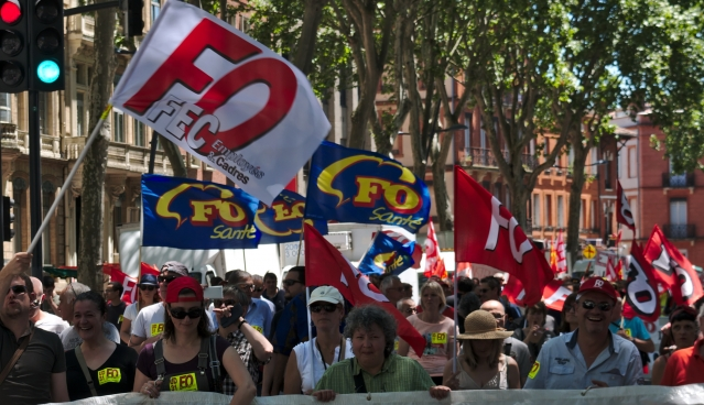 Union members march in the street with FO banners