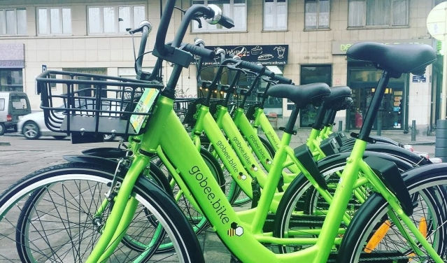 Lime green liveried gobee.bike cycles at a stand, ready for hire