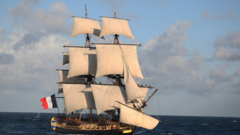 Square-sailed French ship at sea with flag flying