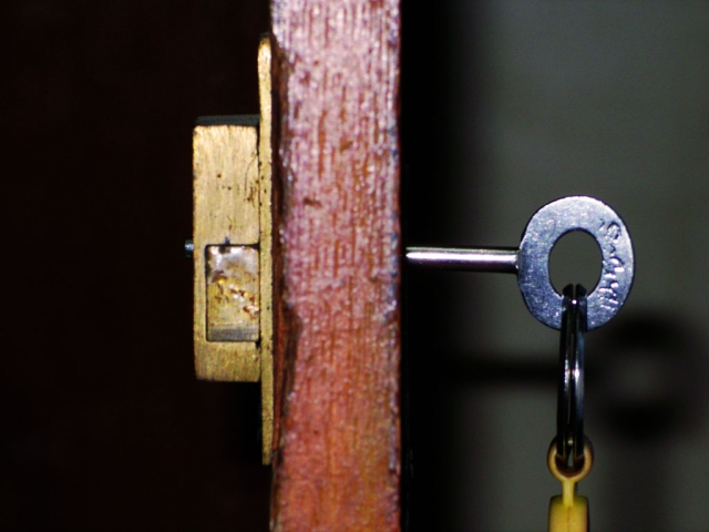 A side-on view of a door, showing the key in one side and the lock on the other