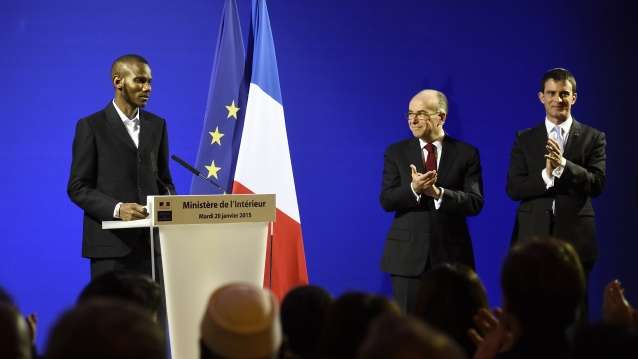 Hyper Cacher hero Lassana Bassily speaks at an event with French ministers standing beside him and French and EU flags