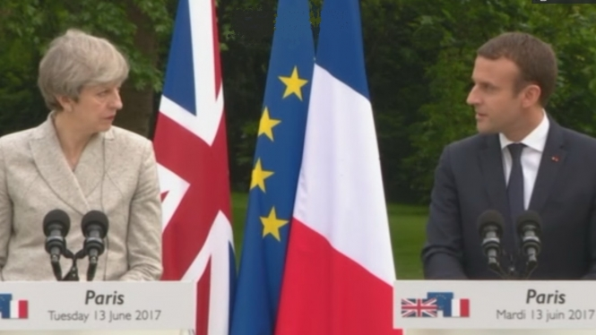 Mr Macron and Mrs May look at each other during a joint statement
