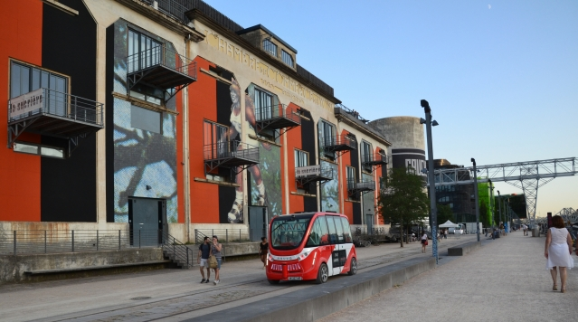 Red-and-white Navly driverless bus on the streets of Lyon