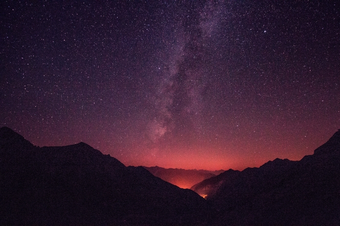 Silhouette of mountains against the backdrop of a starry sky, partially polluted by light from a town