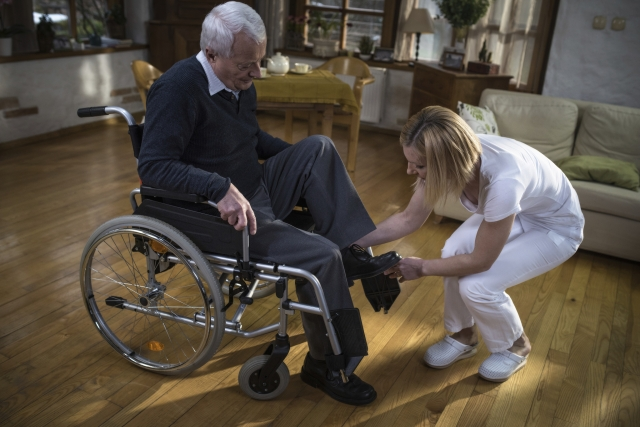 A nurse in uniform helping an elderly, wheelchair-bound, man put on a shoe