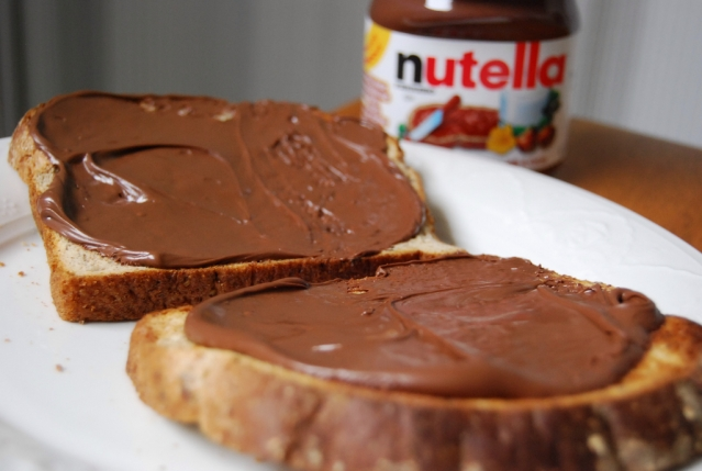 Two slices of toast covered with Nutella spread on a plate, with a jar of the paste in the background