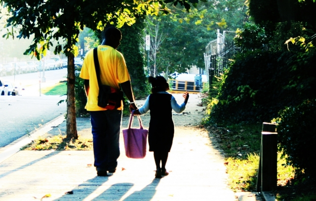 Adult and child walking along a street