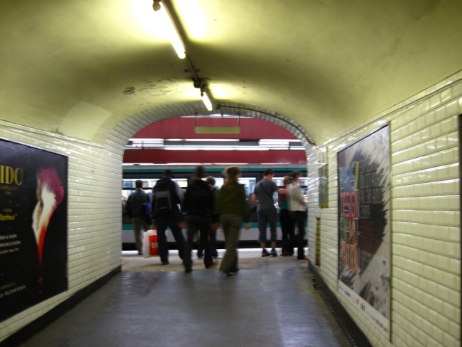 Image taken from behind of commuters using Paris Metro heading out of a tunnel concourse onto one of the underground platforms