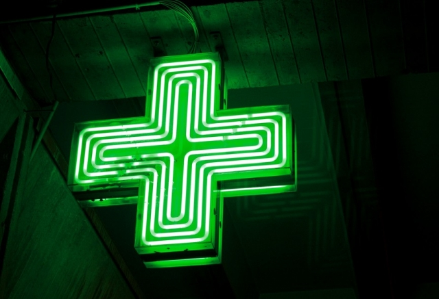 An illuminated neon green cross pharmacy sign against a dark background