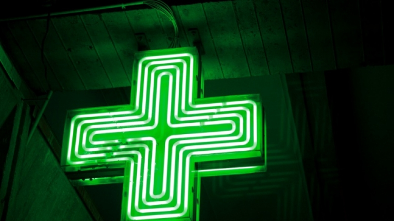 An illuminated neon green cross pharmacy sign against a dark background
