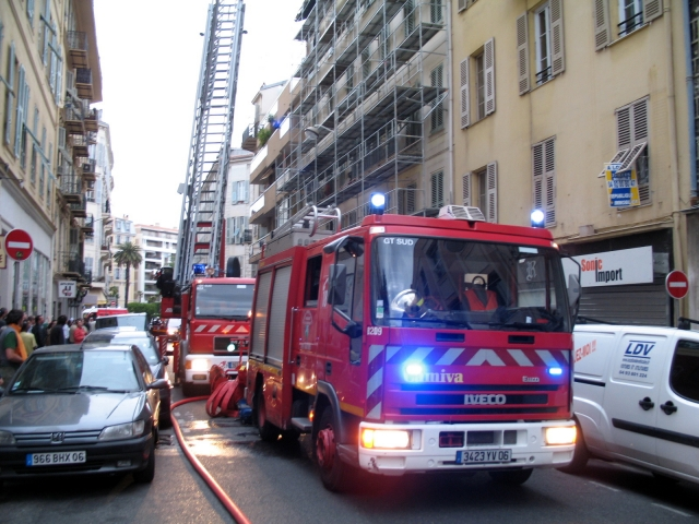 Two French fire engines - one with ladder extended - answering an emergency call