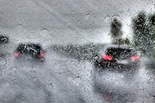 Tail lights of cars in front driving in heavy rain diffused by rain on a vehicle windscreen
