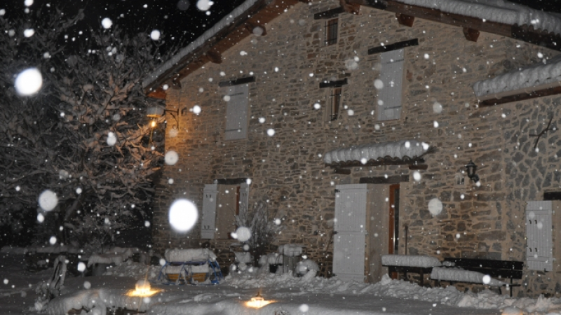 View of a suttered-up house in the Alps in winter as snow falls