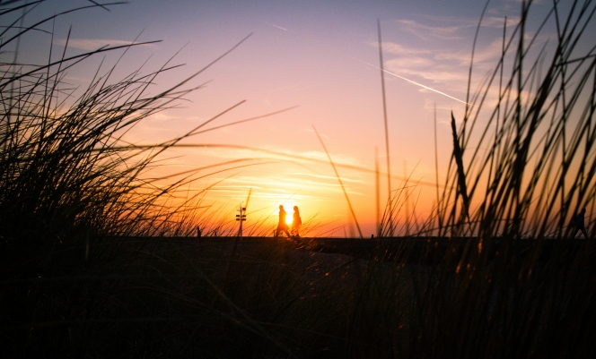 Low shot through grass of silhouettes of a couple walking in the distance framed by the setting sun