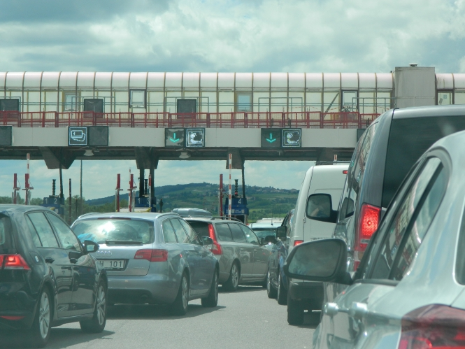 Vehicles queuing to pass a toll booth on to a motorway in southeastern France