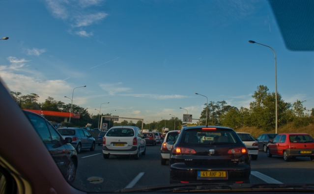 Slow-moving, heavy traffic photographed through the windscreen of a vehicle