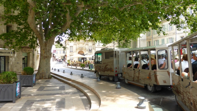 A cream 'road train' packed with tourists travelling along the streets of Avignon