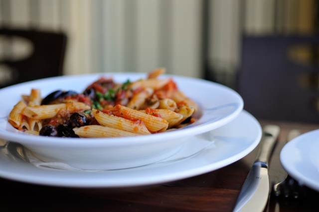 A vegetarian meal of pasta, tomato sauce and olives in a dish